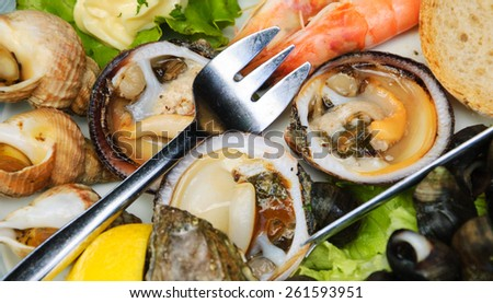 Fresh seafood at seaside cafe in Brittany, France. Selective focus on the fork and opened mussels beside it. - stock photo