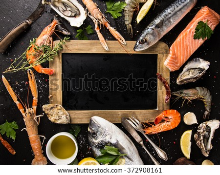 Fresh seafood on black stone with empty sheet, close-up. - stock photo