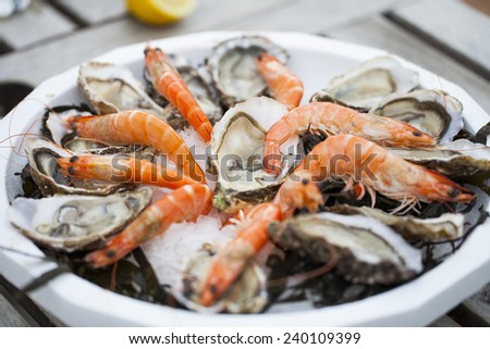 Fresh seafood - Oysters and shrimps on a plate - stock photo