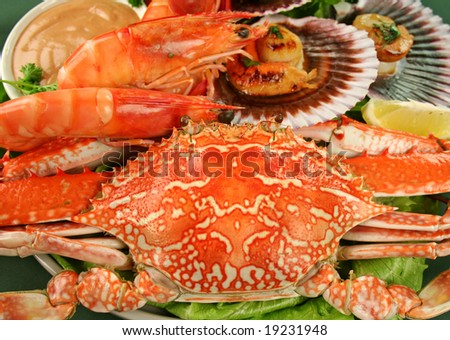 Fresh seafood platter of cooked shrimps, sand crab and pan fried scallops and lemon. - stock photo