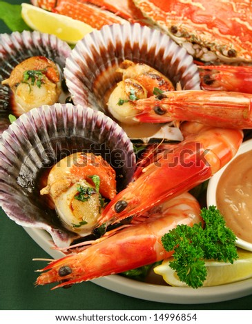Fresh seafood platter of cooked shrimps, sand crab and pan fried scallops with coriander with thousand island dressing. - stock photo