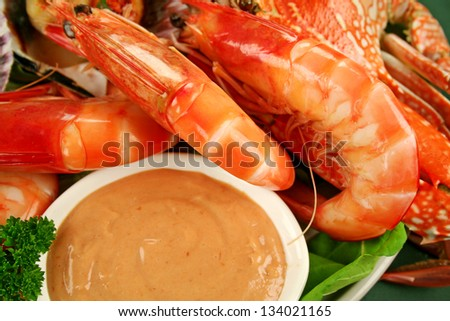 Fresh seafood platter of cooked shrimps, sand crab with coriander with Thousand Island Dressing. - stock photo