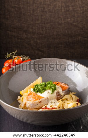 Fresh seasoning pasta with grilled salmon steak in a decor dish. - stock photo