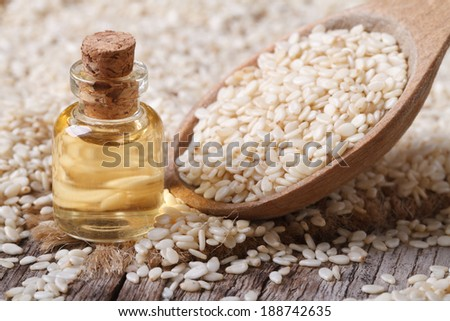 Fresh sesame oil in a glass bottle and seeds in a wooden spoon closeup horizontal  - stock photo