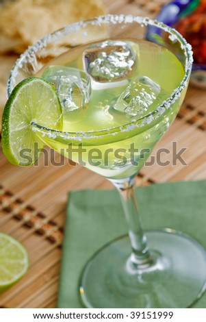 Fresh sharp and tangy margarita on the rocks with salt and lime - shallow DOF on the lime and front rim of the glass