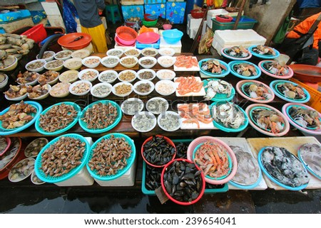 Fresh shellfish for sale in Jagalchi Fish Market under available light - stock photo