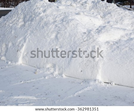 Fresh Shoveled Snow Bank After Storm - Freshly shoveled driveway with snow on the ground and a large pile of white winter snow, close up winter background photo. - stock photo