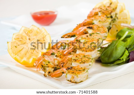 Fresh shrimp skewers on a white plate with citrus, salad and seafood sauce. Shallow depth of field. - stock photo