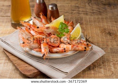 Fresh shrimps on a plate on a wooden background, selective focus