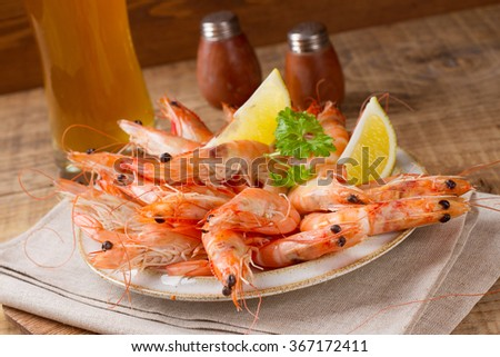 Fresh shrimps on a plate on a wooden background, selective focus - stock photo
