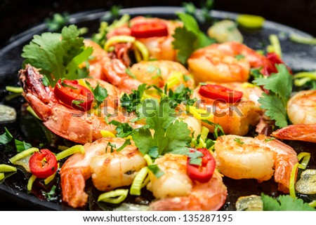 Fresh shrimps on old pan with garlic - stock photo