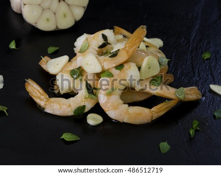 fresh shrimps tails with garlics and fresh thyme on black background