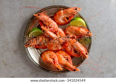 Fresh shrimps with lime on plate, selective focus - stock photo