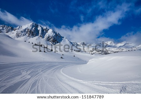 Fresh ski slope and mountains in sunny day - stock photo