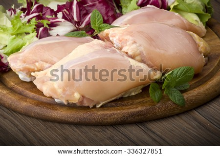 Fresh skinless chicken thighs and legs on cutting board  - stock photo