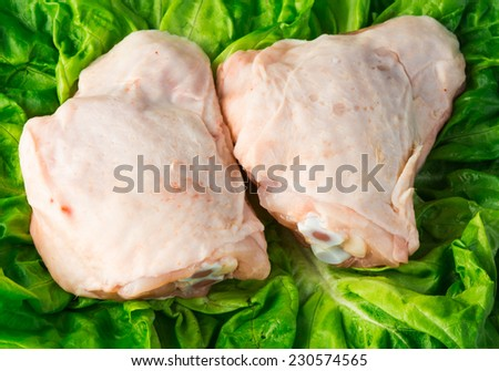 Fresh skinless chicken thighs on salad background - stock photo