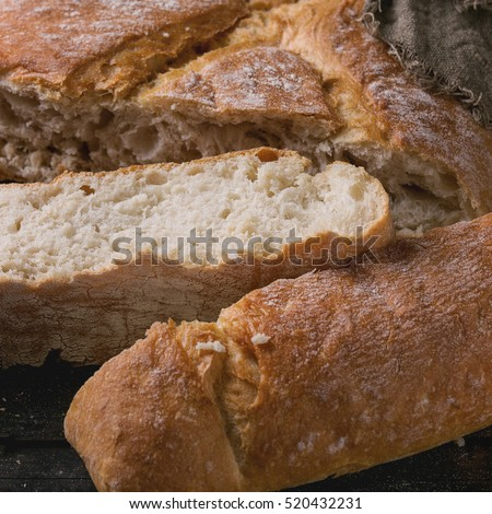 Fresh slice artisan bread under sackcloth old wooden background. Close up. Square image