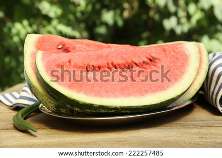 Fresh slice of watermelon on table outdoors, close up - stock photo