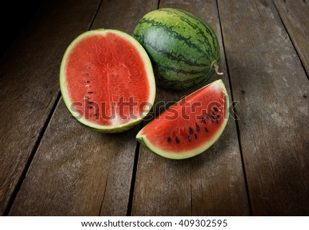 Fresh sliced and half of watermelon on the wooden table - stock photo