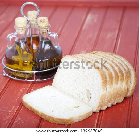 Fresh sliced bread with oil and vinegar on table - stock photo