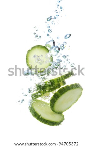 fresh sliced cucumber in water isolated on white - stock photo