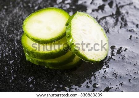 Fresh sliced cucumber  on wet black stone background - stock photo
