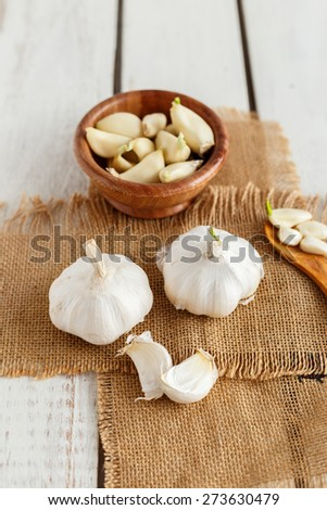Fresh sliced Garlic in a wooden bowl on a white wood background - stock photo