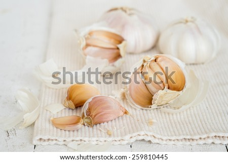 Fresh sliced garlic in on white wooden background - stock photo