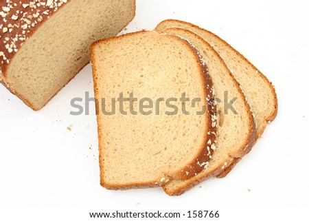 Fresh sliced honey wheat bread sprinkled with rolled oats.
