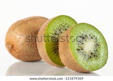 Fresh sliced kiwi fruits on white background with reflection - stock photo