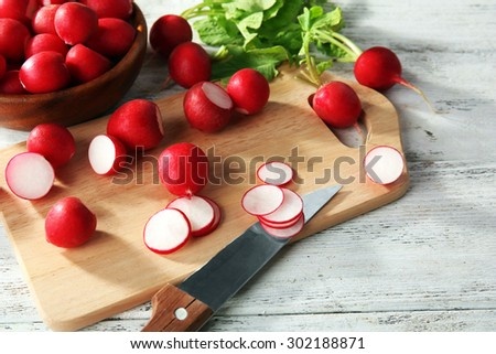 Fresh sliced radishes on cutting board close up - stock photo