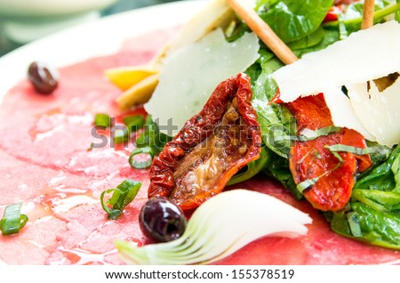 Fresh Sliced raw beef meat with leaf lettuce on the table  - stock photo