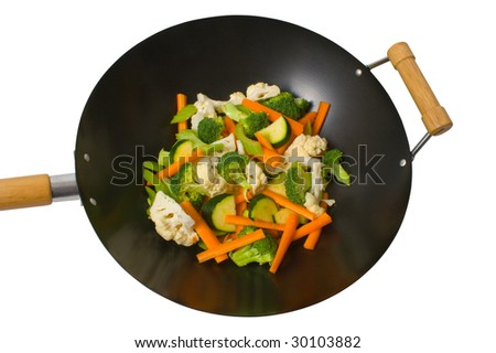 Fresh sliced vegetables in wok over white background. - stock photo