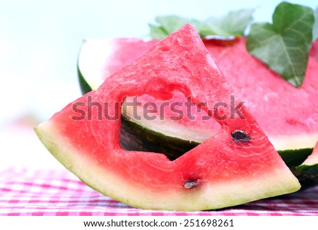 Fresh slices of watermelon on table, on blue background - stock photo
