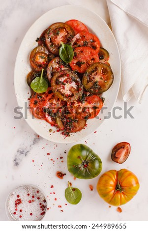 Fresh slices tomatoes salad with fresh herbs. Healthy food from garden. Food blue background.  - stock photo