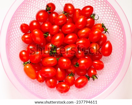 fresh small tomatoes in pink plastic basket