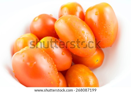 Fresh small tomatoes with white cup on white background