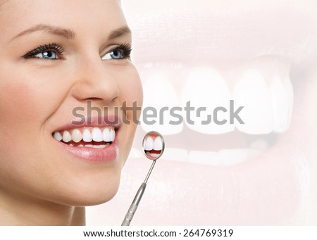 Fresh smile. Teeth whitening. Oral check up. Portrait of young cheerful woman examining her teeth with dental mirror.  - stock photo