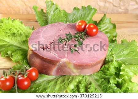 Fresh smoked ham on lettuce with spices - stock photo