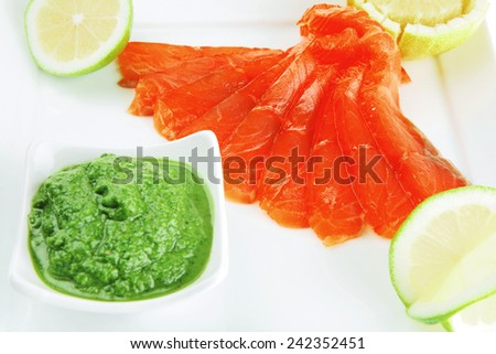 fresh smoked salmon on white plate with green sauce - stock photo