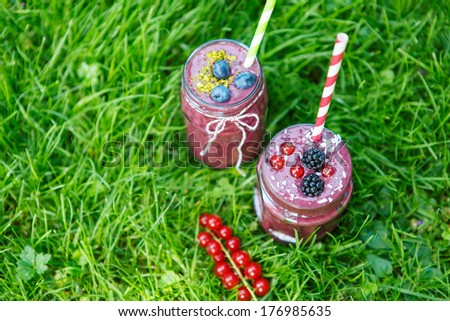 Fresh smoothie drink with different berries as healthy breakfast. On green grass background - stock photo
