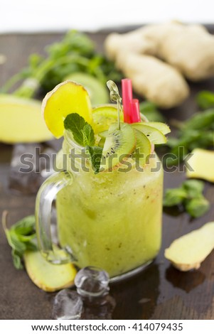 Fresh smoothie with cucumber ginger and kiwi on a wooden table - stock photo