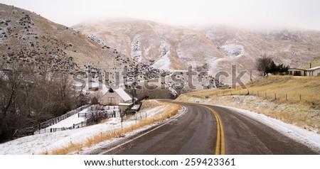 Fresh Snow Blankets Hillside Rural Country Scene Two Lane Road - stock photo