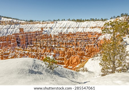 Fresh snow decorates the hoodoos in Bryce National Park and leaves a blanket around the edges of the canyon to create a beautiful scene - stock photo