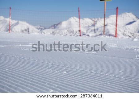 Fresh snow groomer tracks on a mountain ski piste - stock photo