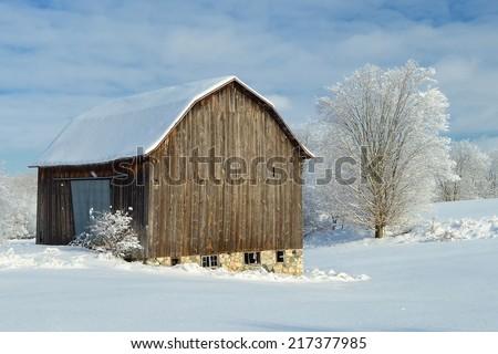 Fresh snow on an old barn in rural Michigan - stock photo