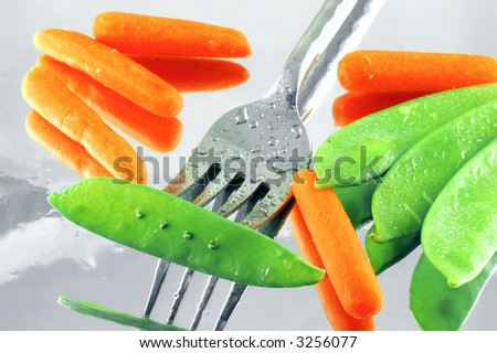 Fresh snow peas and baby carrots on a mirrored background with a fork
