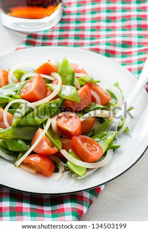 Fresh snow peas and tomato salad on plate, vertical - stock photo