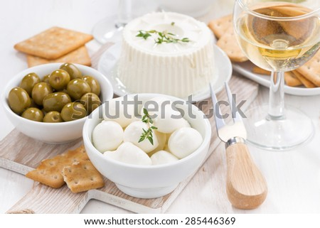 fresh soft cheeses, crackers and pickles to wine, close-up, horizontal - stock photo