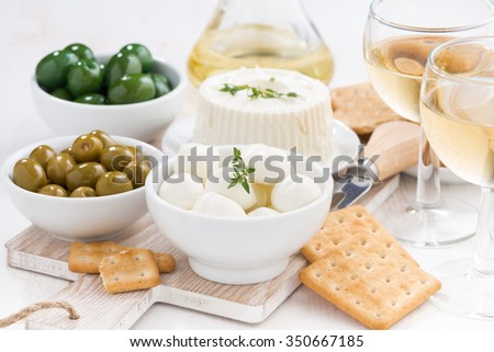 fresh soft cheeses, crackers and pickles to wine on table, horizontal - stock photo